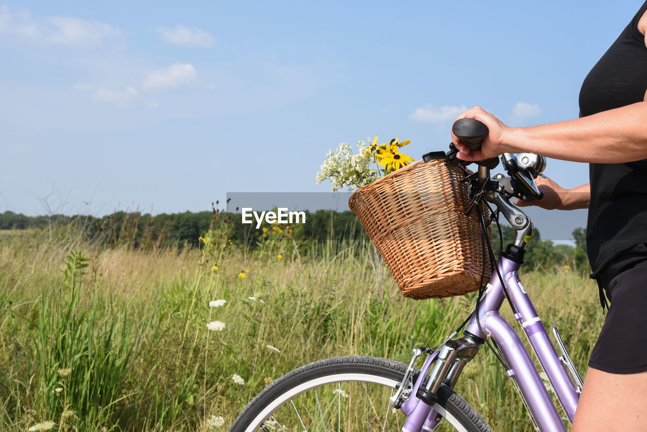 Midsection of woman with bicycle walking on land