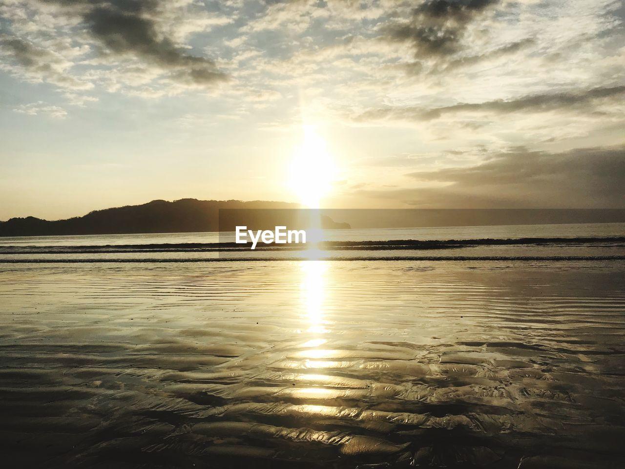 sky, beauty in nature, cloud - sky, water, sunset, scenics - nature, tranquility, tranquil scene, sea, reflection, sun, nature, sunlight, idyllic, no people, beach, land, horizon over water, non-urban scene, outdoors