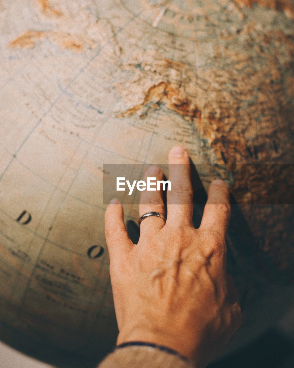 Close-Up Of Human Hand On Globe