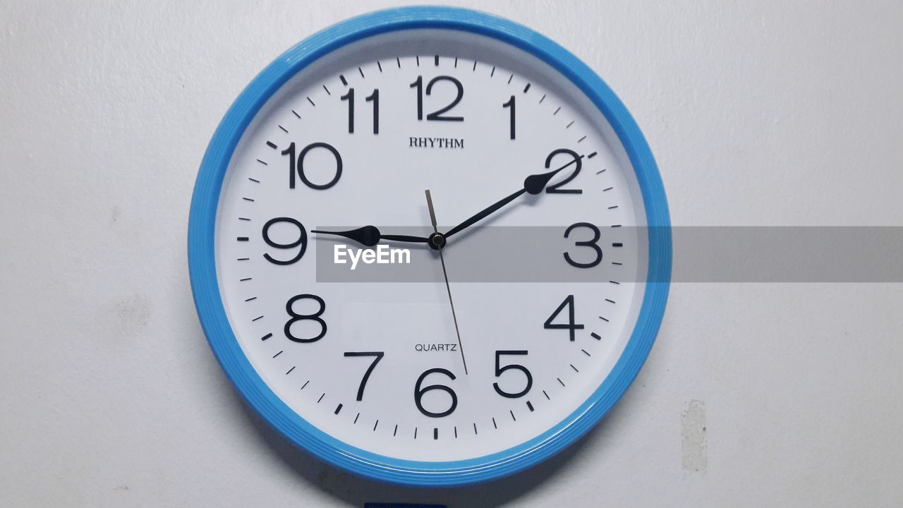 clock, time, number, wall - building feature, circle, geometric shape, indoors, close-up, no people, blue, shape, minute hand, communication, instrument of time, accuracy, wall clock, white color, clock face, table, wall, hour hand