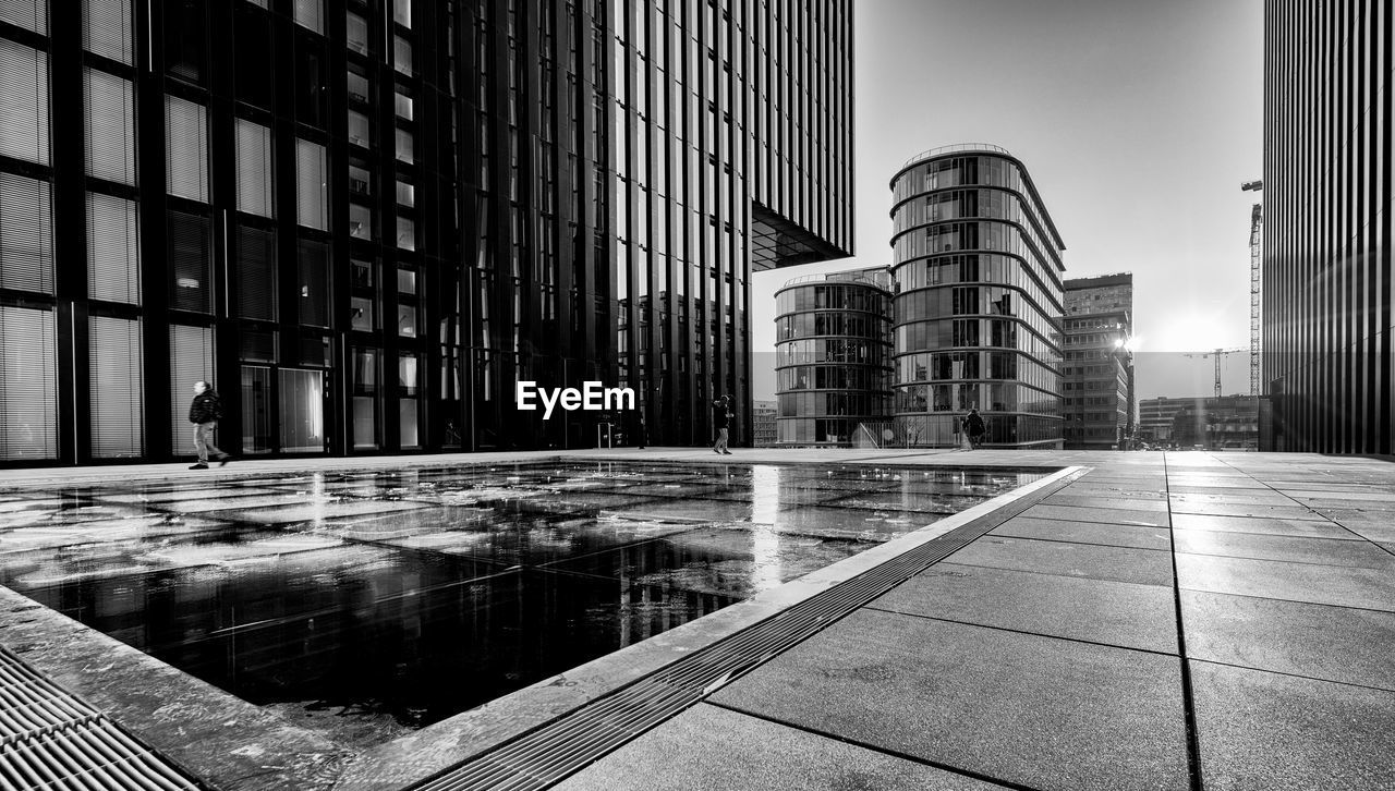 architecture, built structure, building exterior, city, building, reflection, office, office building exterior, modern, nature, no people, day, sky, glass - material, street, tall - high, water, outdoors, tower, skyscraper, financial district, tiled floor
