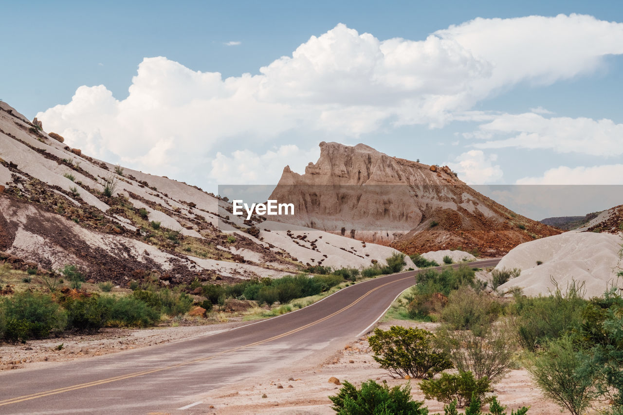 sky, mountain, cloud - sky, road, landscape, environment, non-urban scene, transportation, beauty in nature, tranquil scene, scenics - nature, tranquility, nature, the way forward, no people, day, direction, mountain range, land, desert, arid climate, outdoors, climate, formation