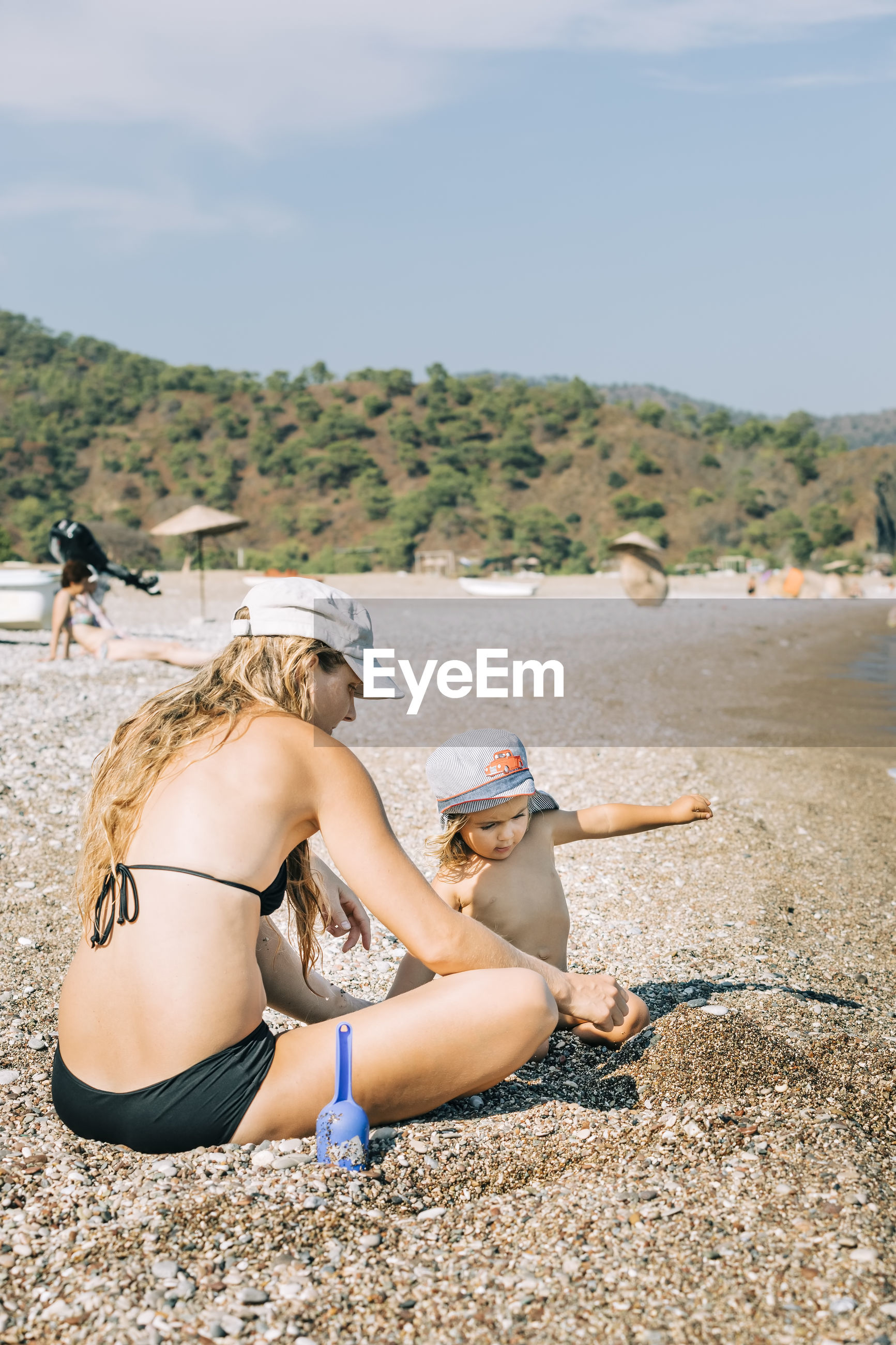 YOUNG WOMAN SITTING ON BEACH WITH UMBRELLA