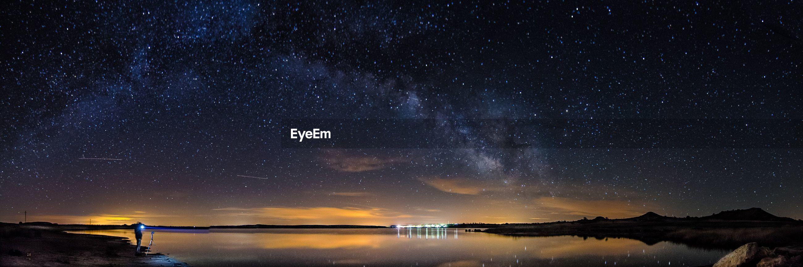 Panoramic view of lake against star field at night