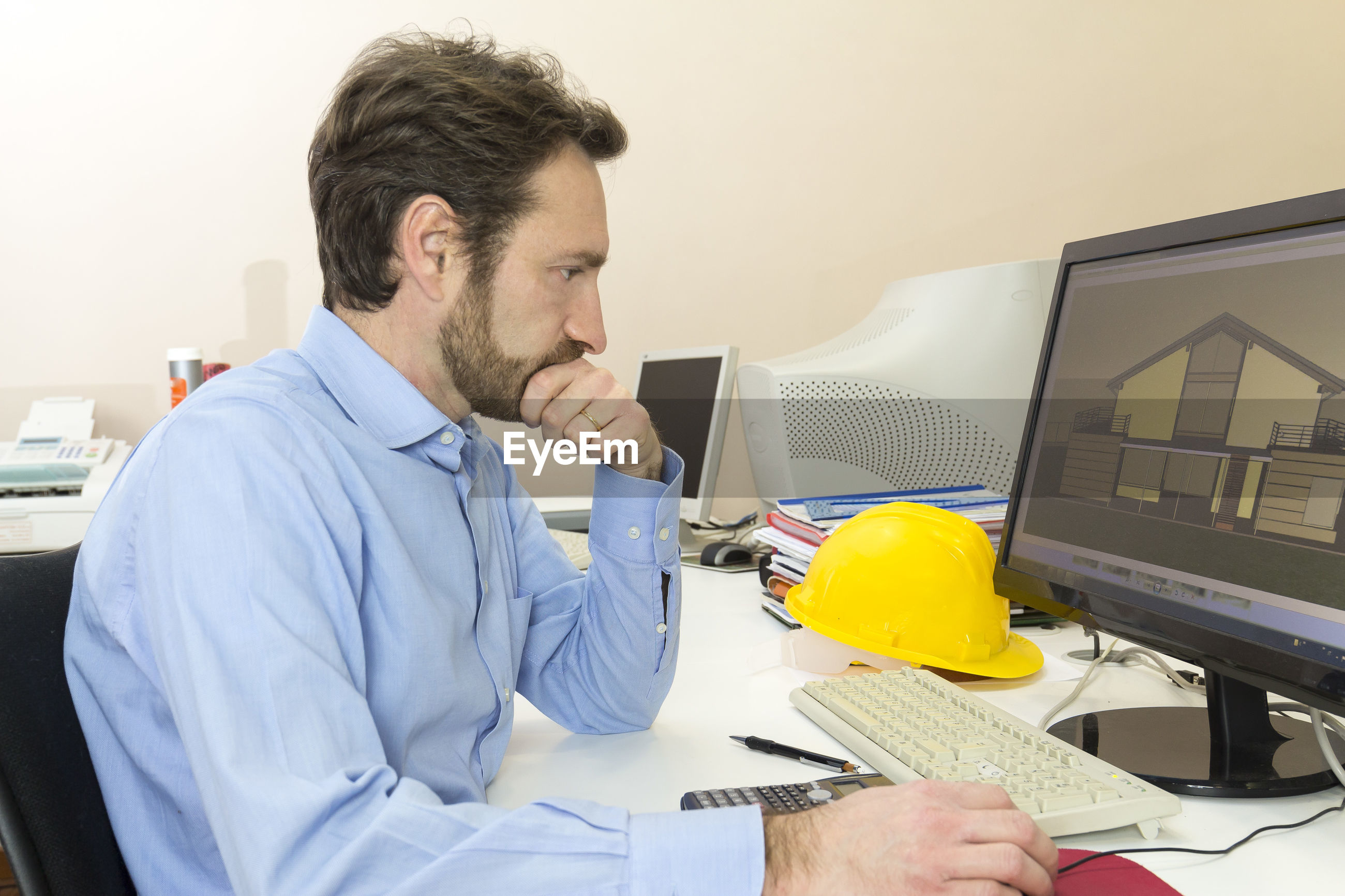 Side view of architect using computer on table at office