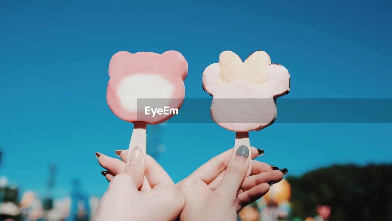 Cropped hand of female friends holding popsicles against clear blue sky