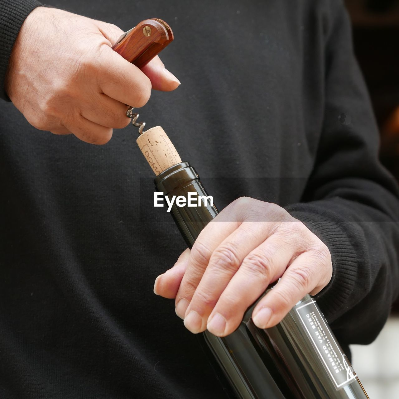 Midsection Of Man Opening Wine Bottle Through Corkscrew