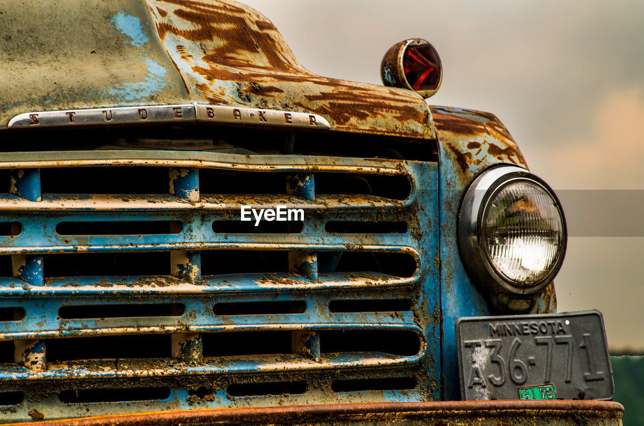 mode of transportation, transportation, metal, land vehicle, abandoned, rusty, day, old, headlight, motor vehicle, obsolete, no people, damaged, car, close-up, run-down, outdoors, nature, sky, deterioration