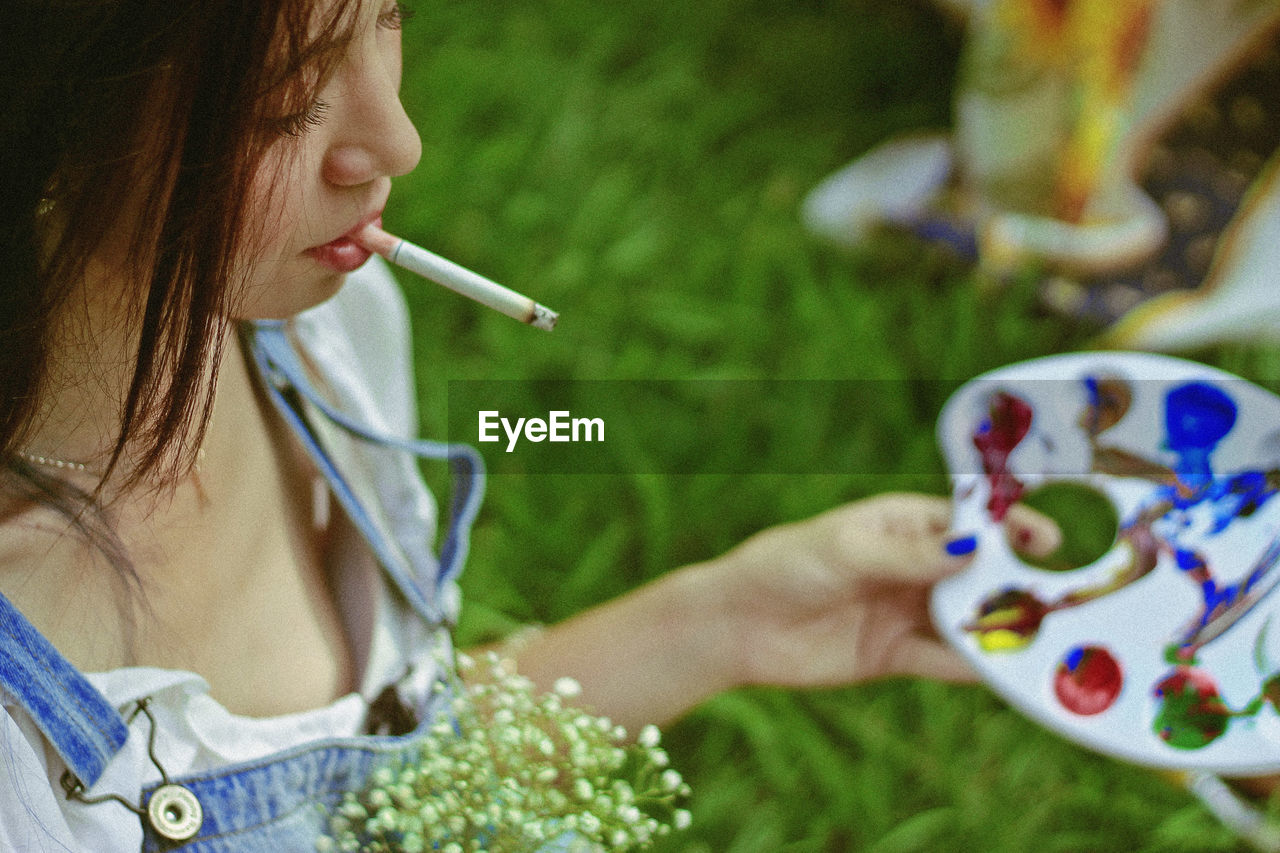 Woman Smoking Cigarette While Holding Color Palette