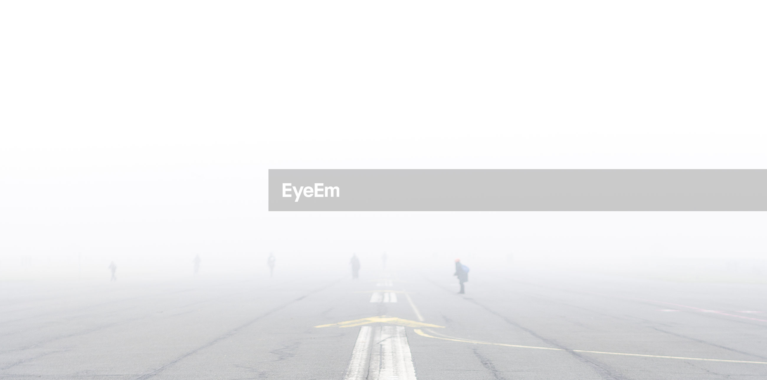 PEOPLE WALKING ON ROAD IN FOGGY WEATHER