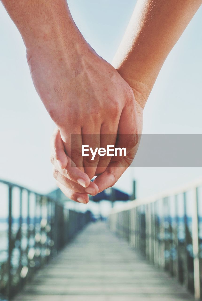 Cropped hand of couple holding hands on pier