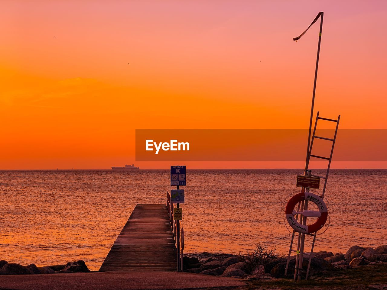 sunset, sky, water, orange color, sea, beauty in nature, scenics - nature, tranquility, horizon over water, horizon, tranquil scene, nature, idyllic, street light, no people, beach, outdoors, land, lighting equipment, sailboat