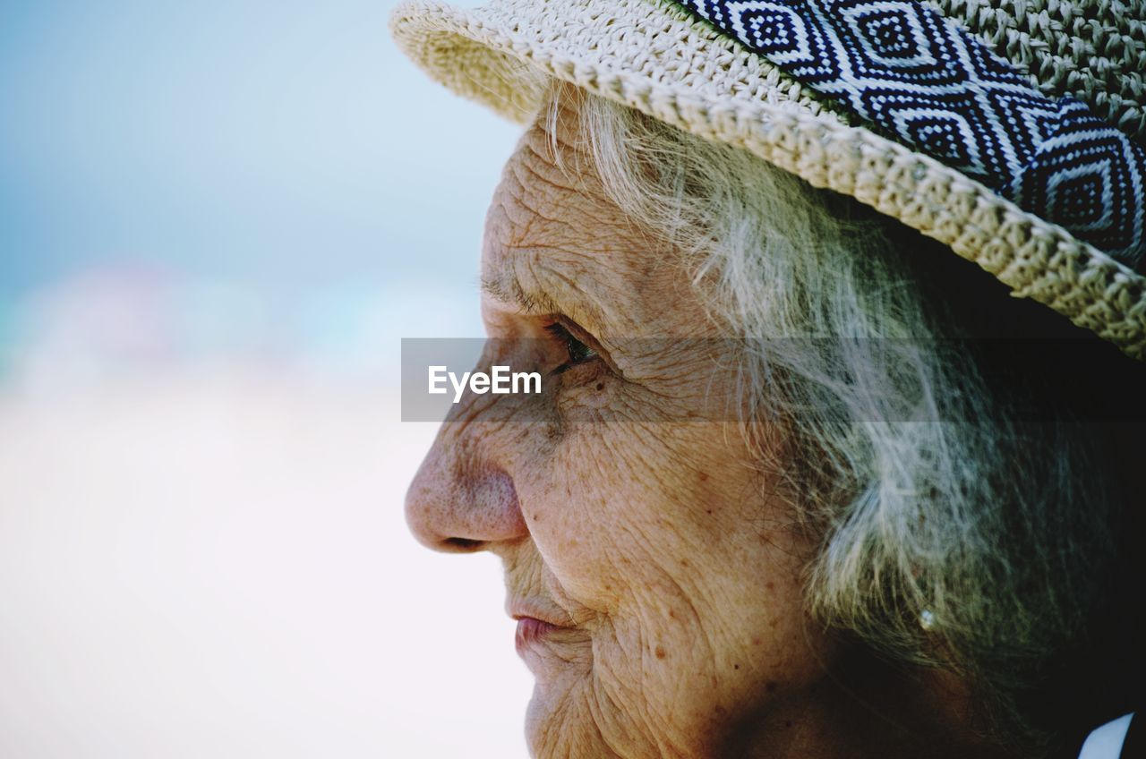 Close-up side view of senior woman wearing hat