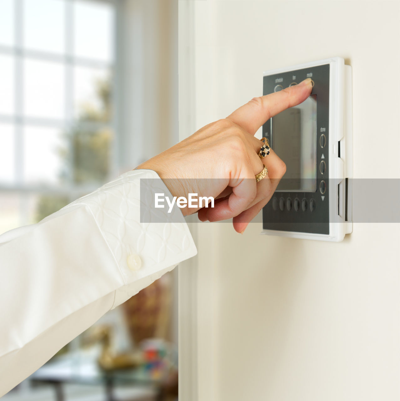 Cropped Hand Using Intercom At Home