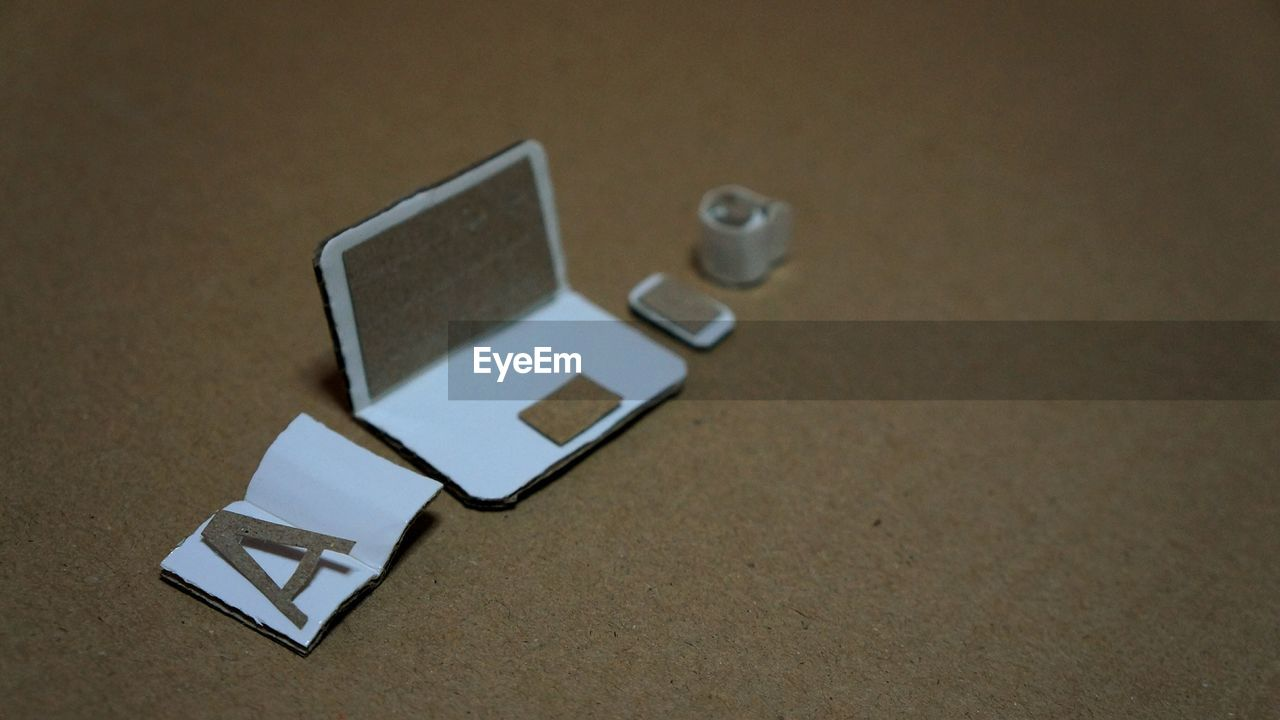 High Angle View Of Artificial Laptop With Book And Cell Phone On Table