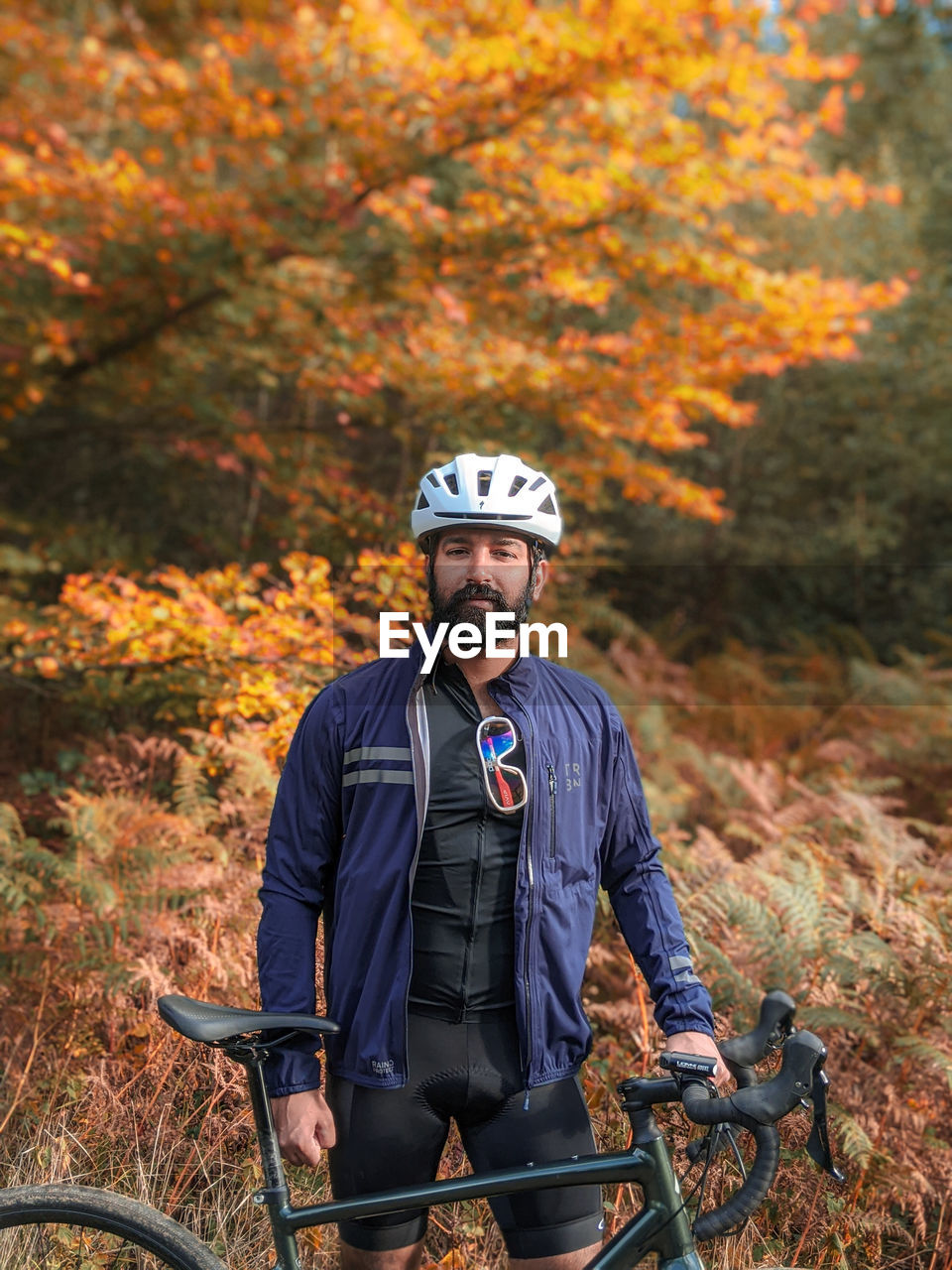 YOUNG MAN RIDING BICYCLE IN AUTUMN