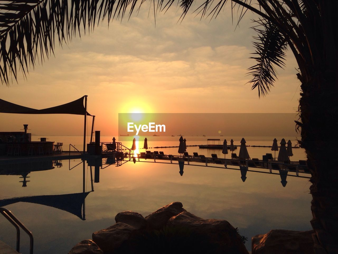 sunset, water, silhouette, nature, sun, beauty in nature, scenics, orange color, sea, sky, reflection, tranquility, palm tree, tree, outdoors, tranquil scene, nautical vessel, travel destinations, swimming pool, men, real people, day, people