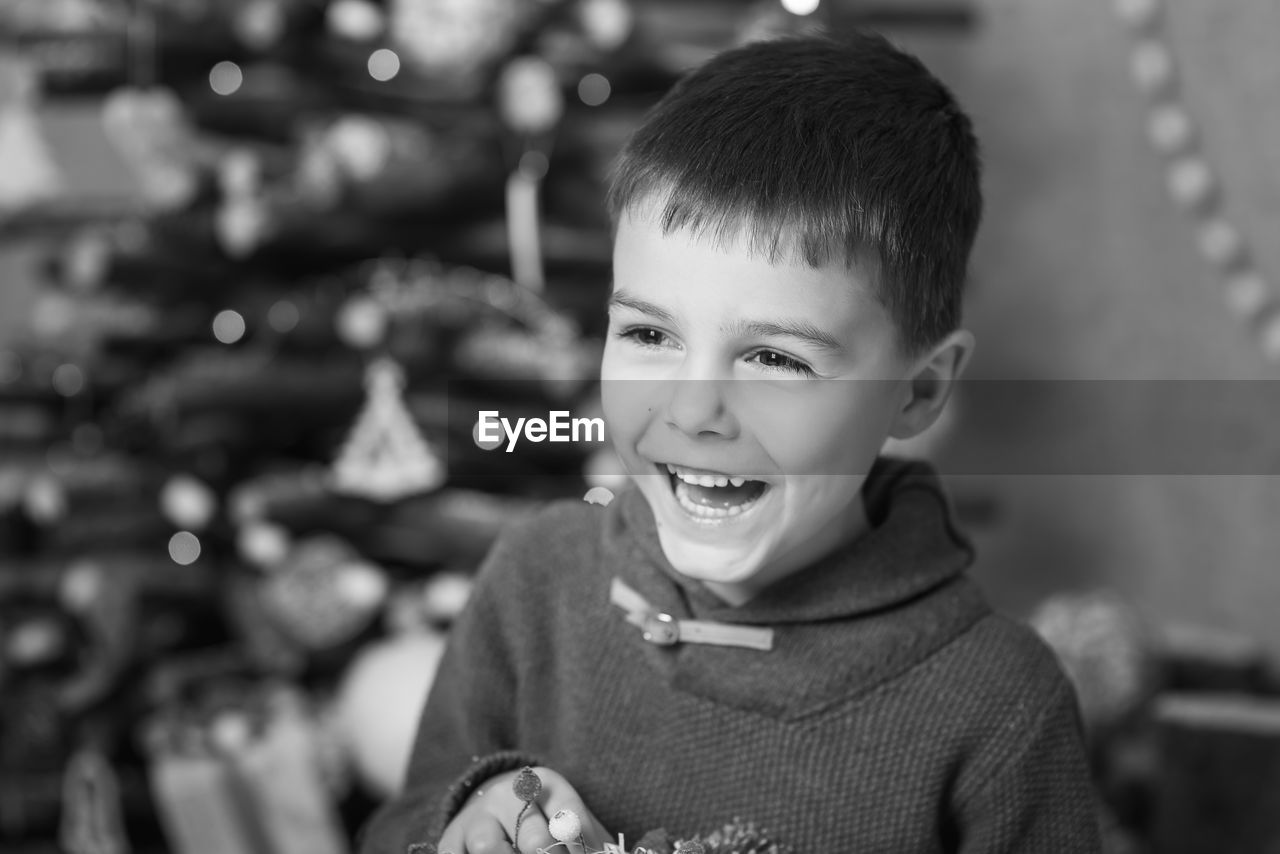 Close-Up Of Cheerful Boy Standing Against Christmas Tree