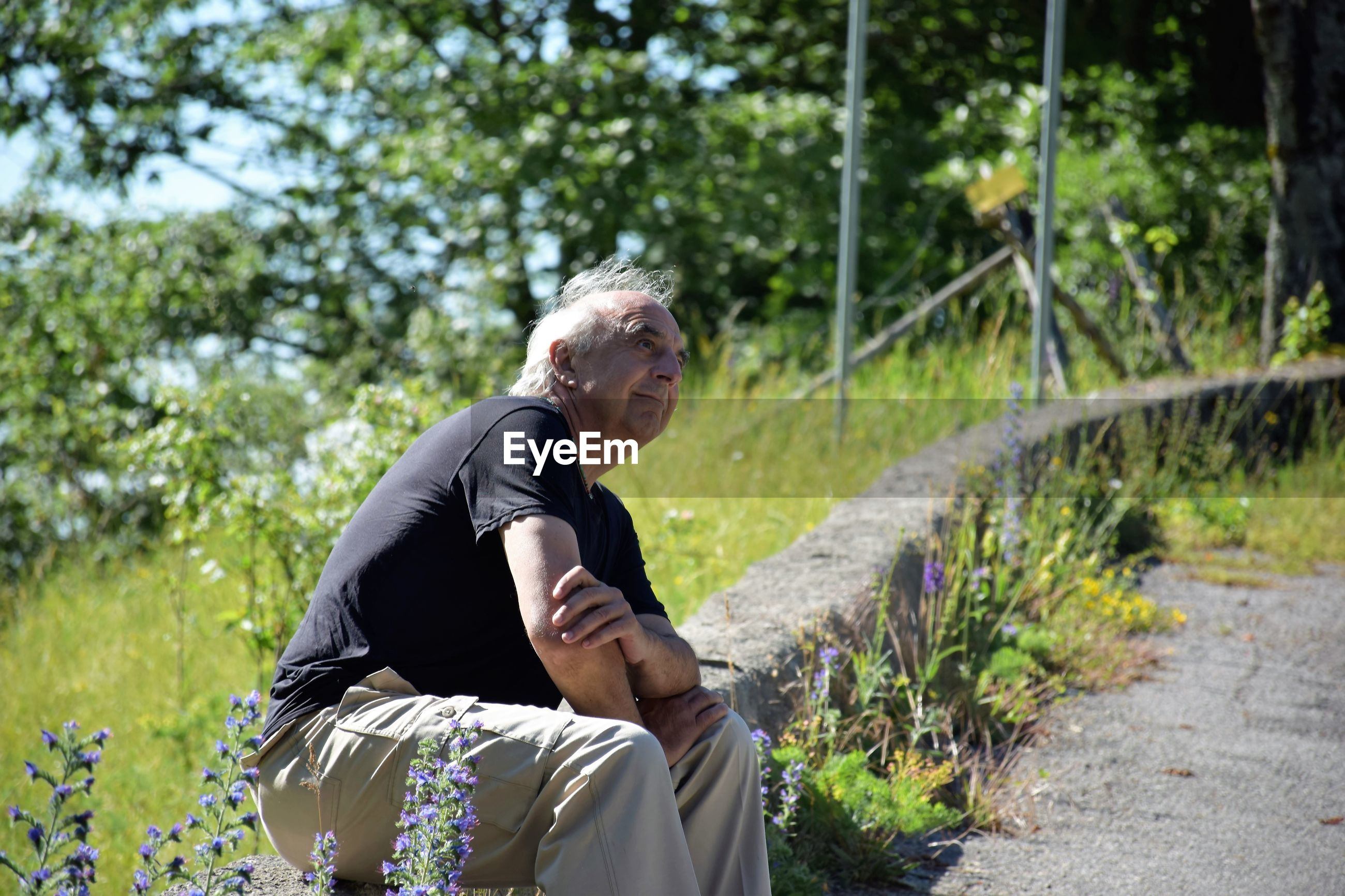 Side view of senior man sitting on retaining wall against trees