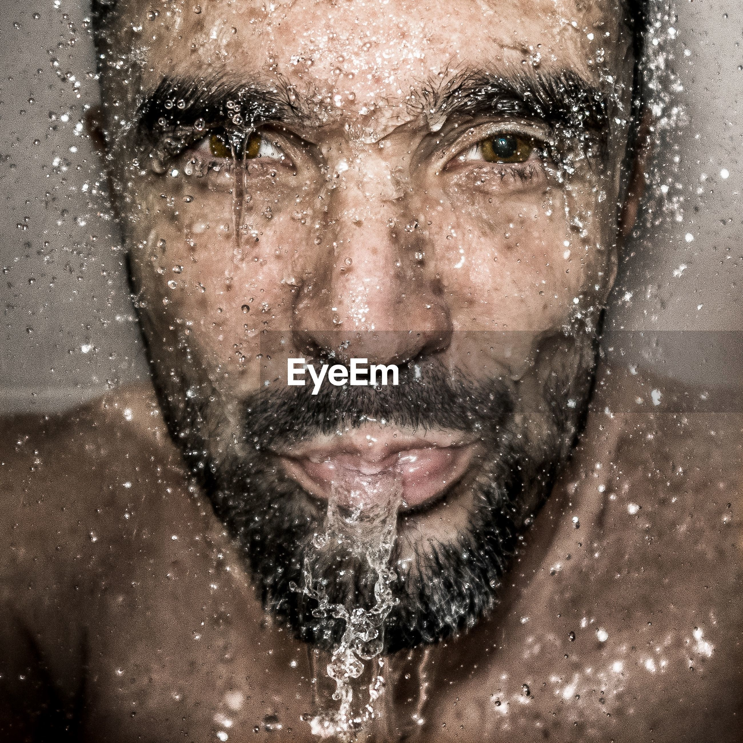 Close-up portrait of mature man spitting water