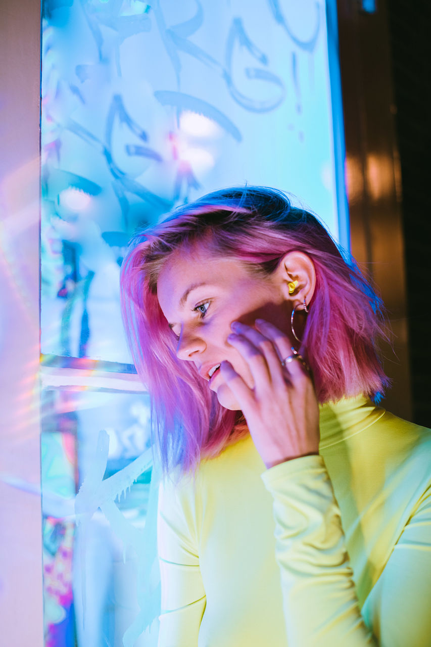 Beautiful young woman with dyed hair in illuminated room