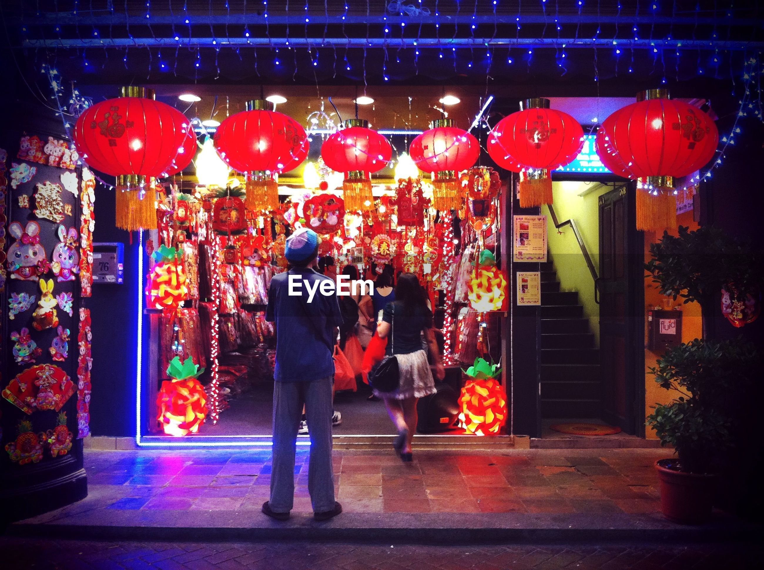 illuminated, night, men, celebration, tradition, person, cultures, red, architecture, built structure, full length, lifestyles, building exterior, leisure activity, decoration, religion, lantern, rear view, standing