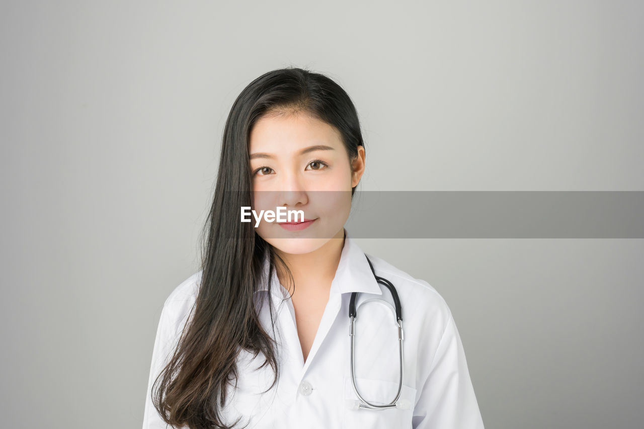 Close-Up Portrait Of Female Doctor With Stethoscope Against White Background