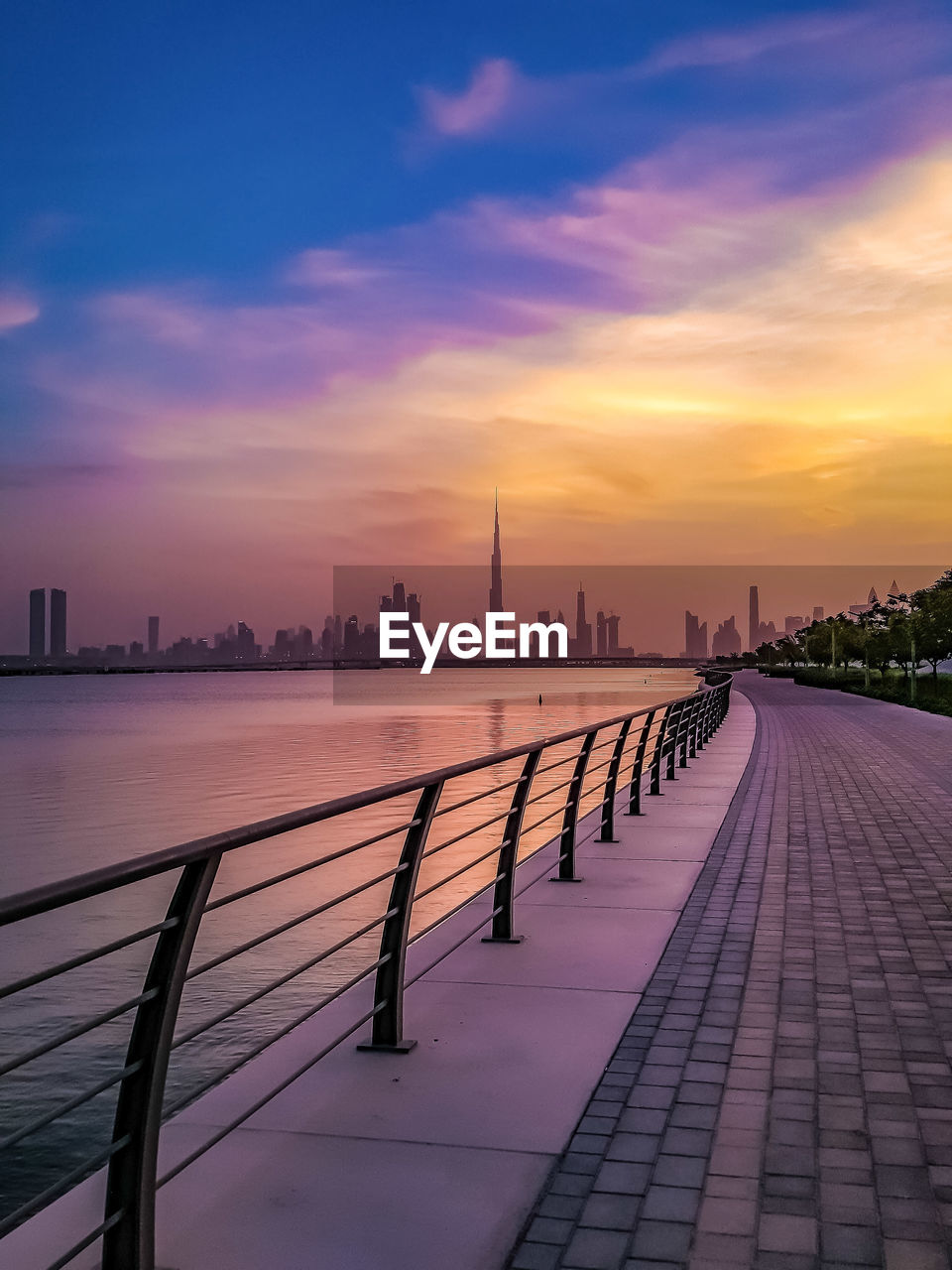 sky, sunset, architecture, built structure, building exterior, city, cloud - sky, railing, water, building, nature, orange color, the way forward, river, no people, direction, footpath, beauty in nature, office building exterior, outdoors, skyscraper, cityscape, promenade
