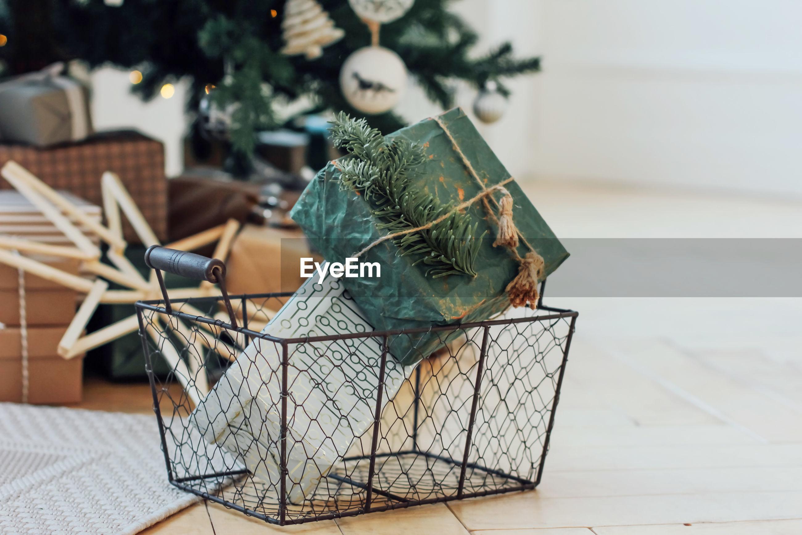 Close-up of gifts in metallic basket on hardwood floor