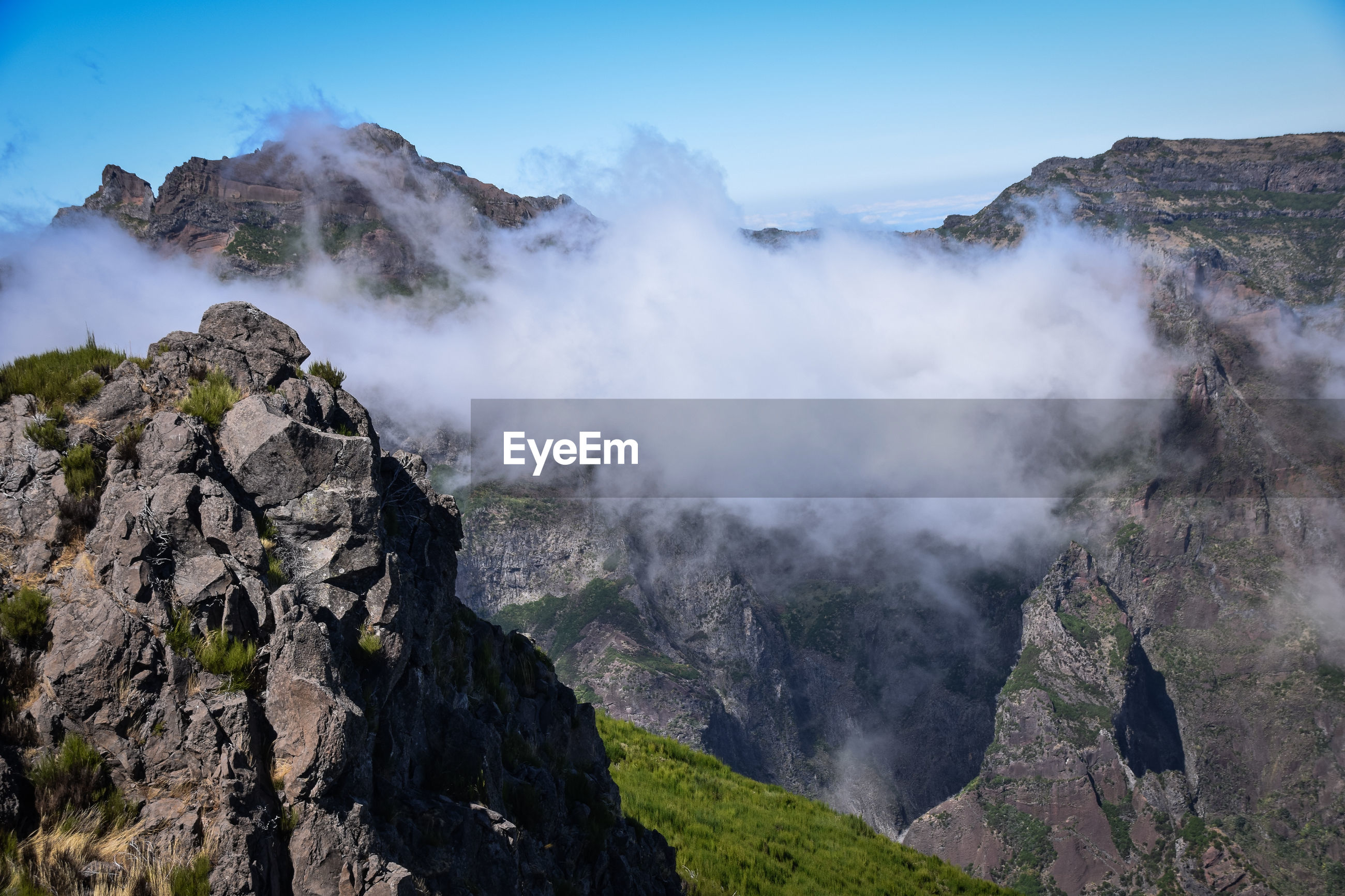 Scenic view of clouds by rocky mountains at pico do arieiro