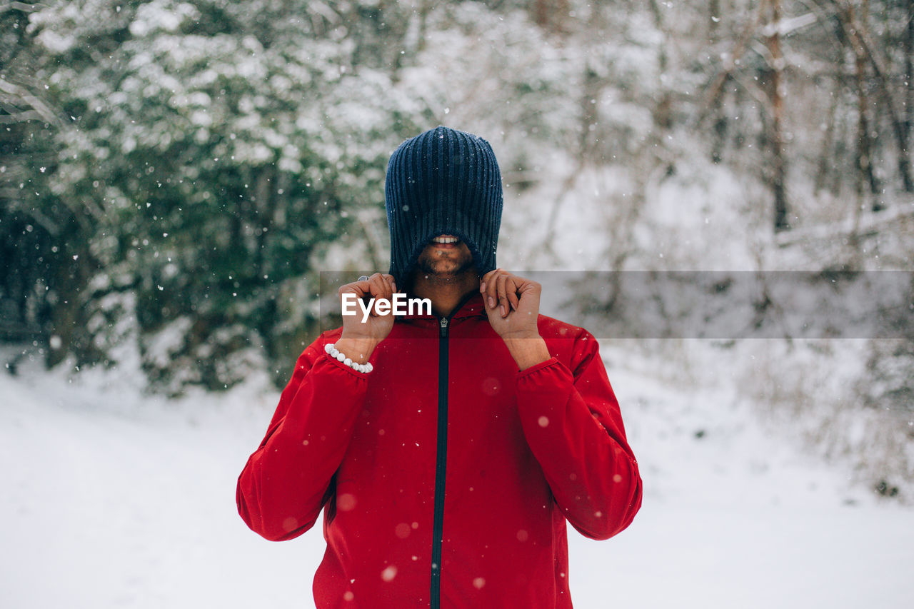 Smiling Young Man Covering Face With Knit Hat In Forest During Snowfall
