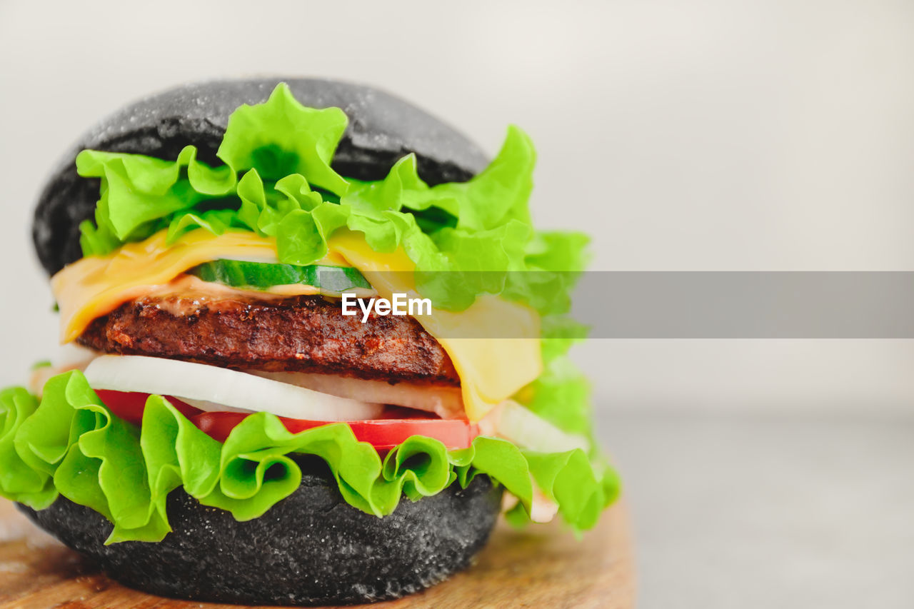 food, food and drink, sandwich, ready-to-eat, lettuce, vegetable, fast food, meat, freshness, healthy eating, still life, indoors, close-up, burger, no people, studio shot, hamburger, focus on foreground, selective focus, meal, bun, take out food, cheeseburger, temptation, snack