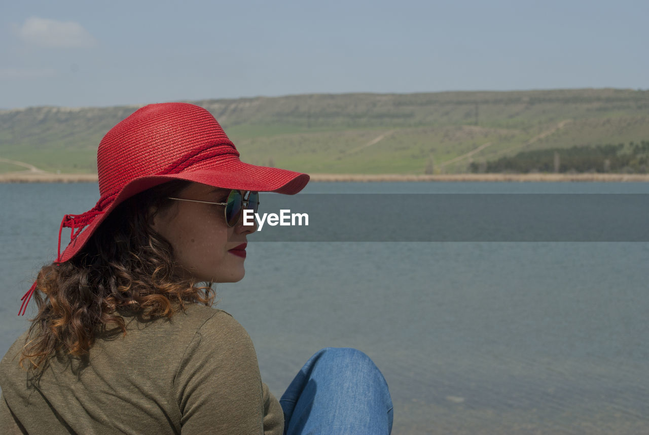 Woman in red cap and sunglasses sitting against lake