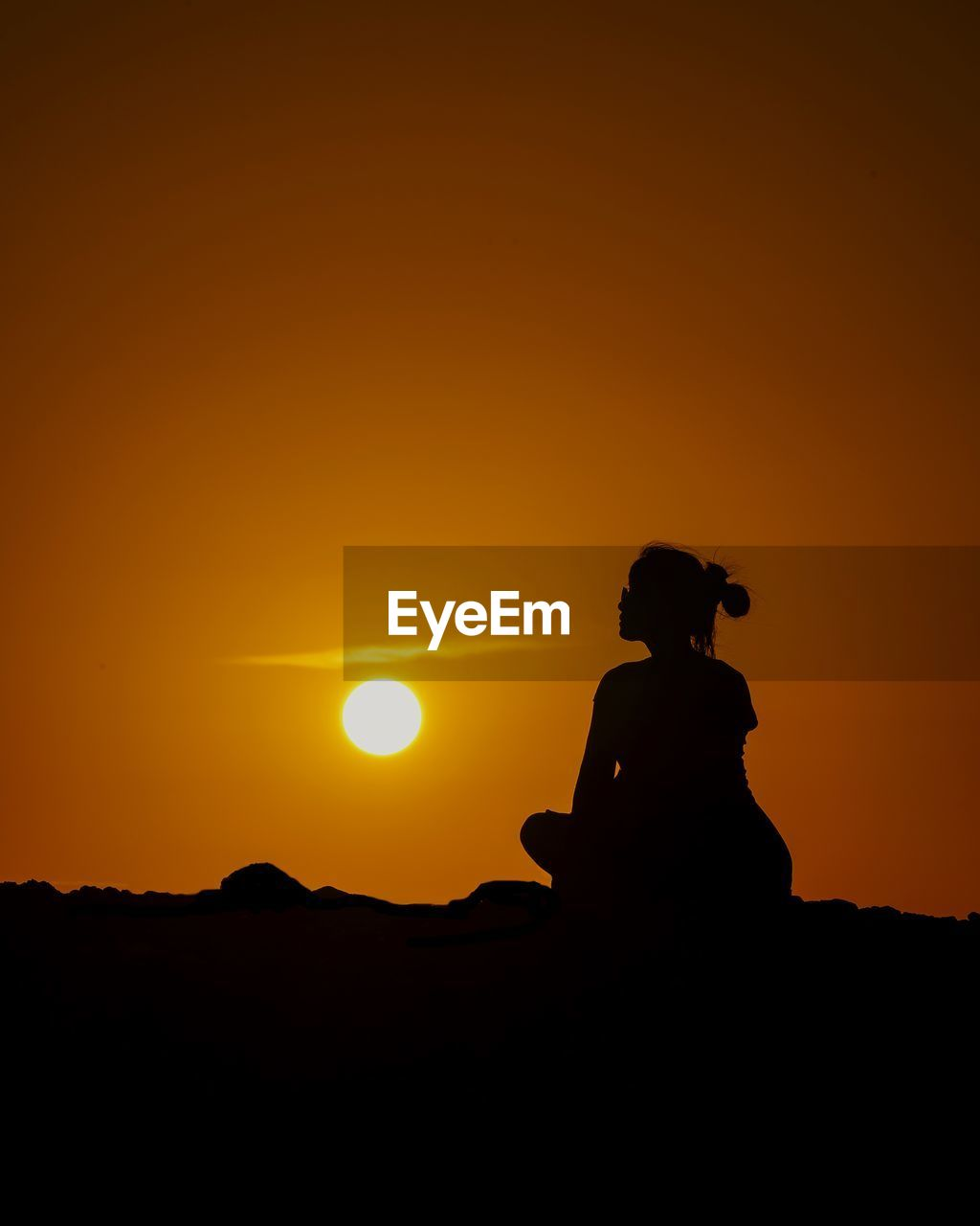 SILHOUETTE MAN SITTING AGAINST ORANGE SUNSET SKY