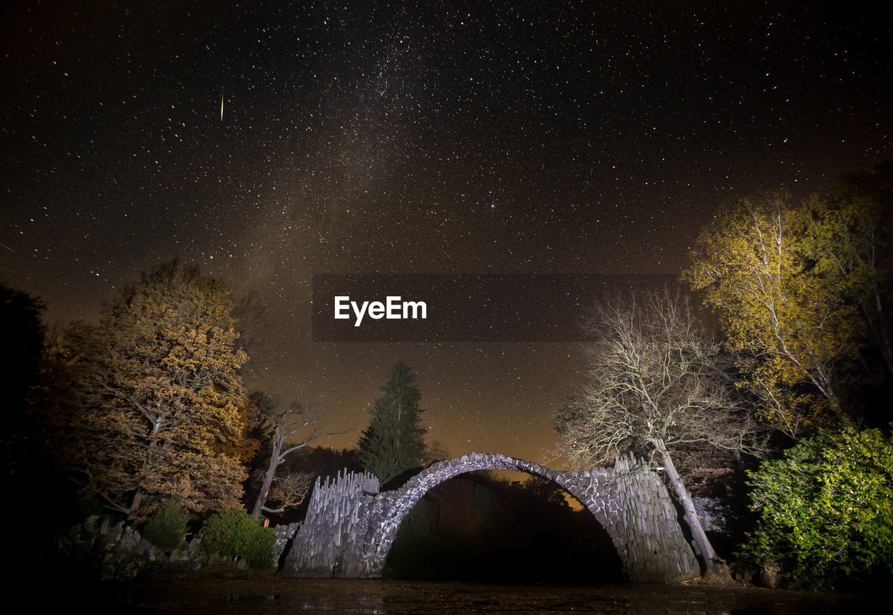Arch bridge over river against star field at night