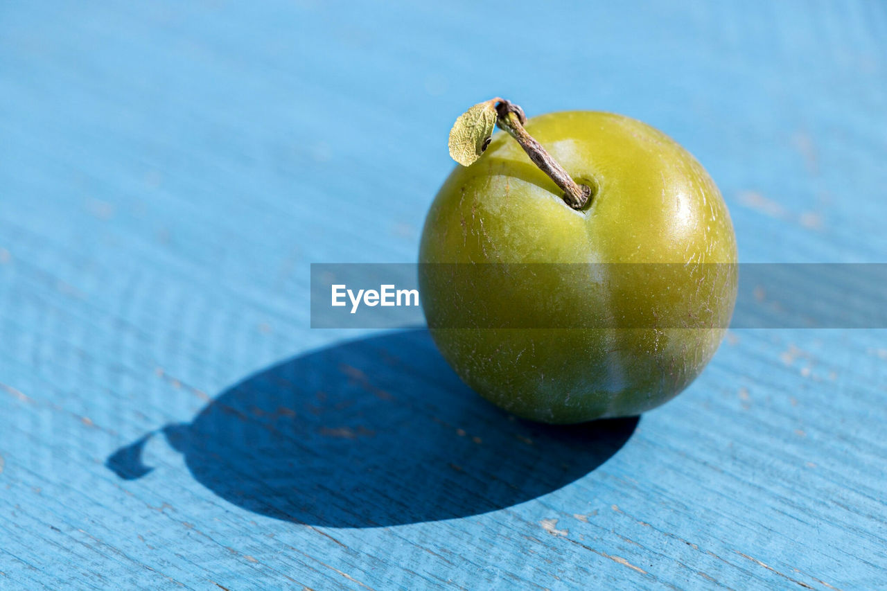 fruit, healthy eating, food, food and drink, wellbeing, table, freshness, wood - material, close-up, apple - fruit, still life, no people, indoors, green color, shadow, day, sunlight, apple, single object, plant stem, ripe