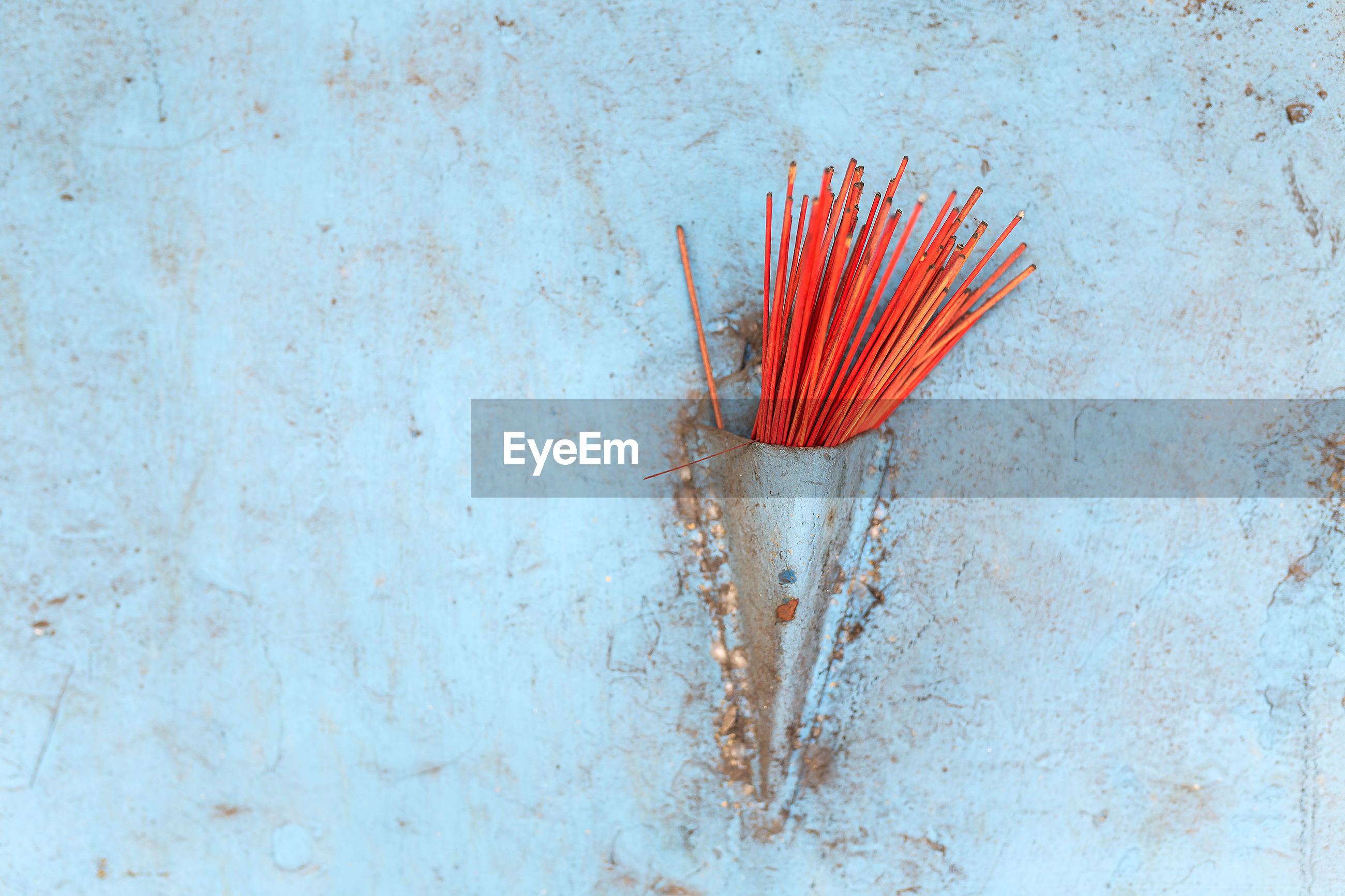 Close-up of incense against blue wall