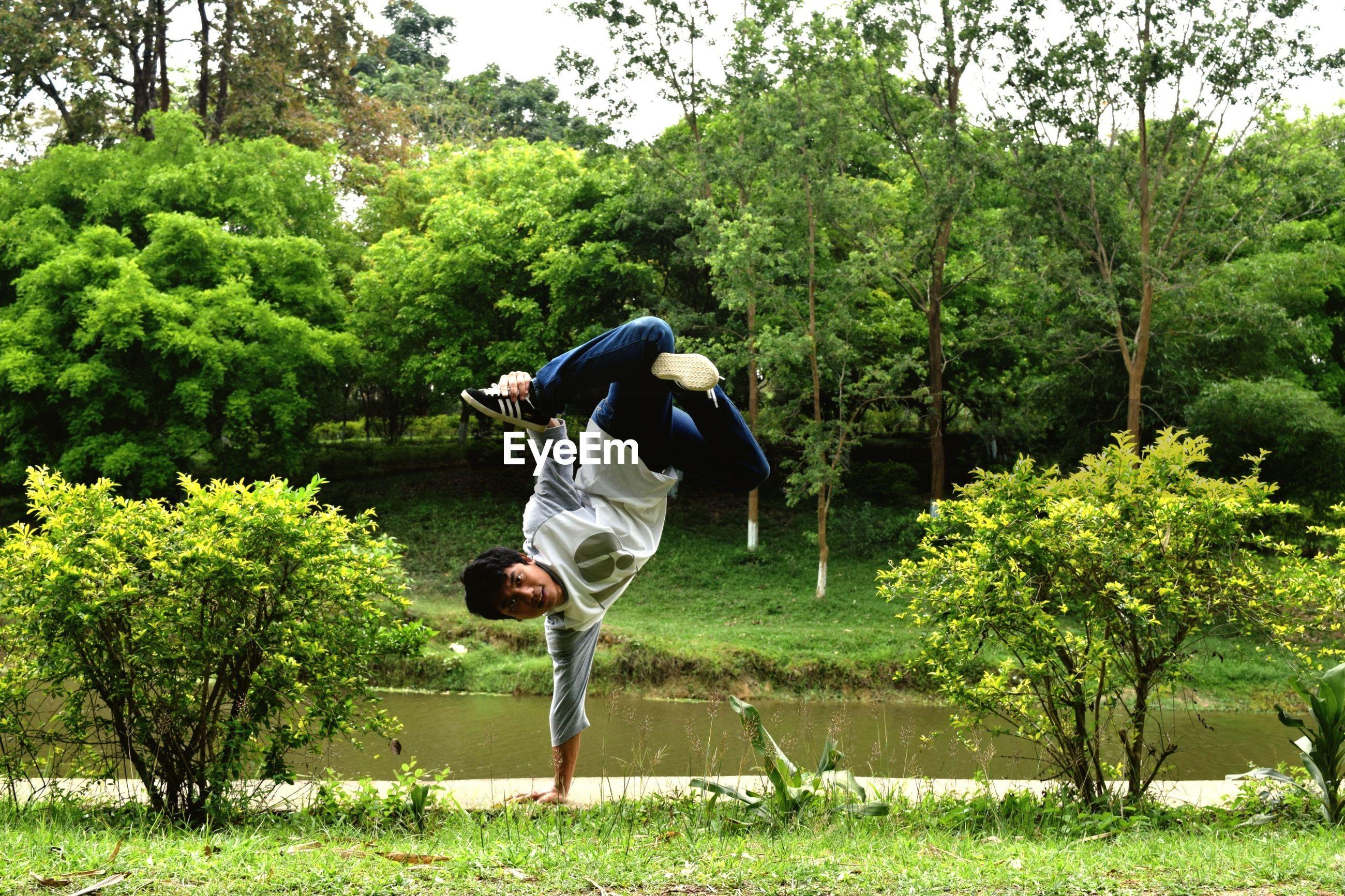 Man practicing stunt against trees in park