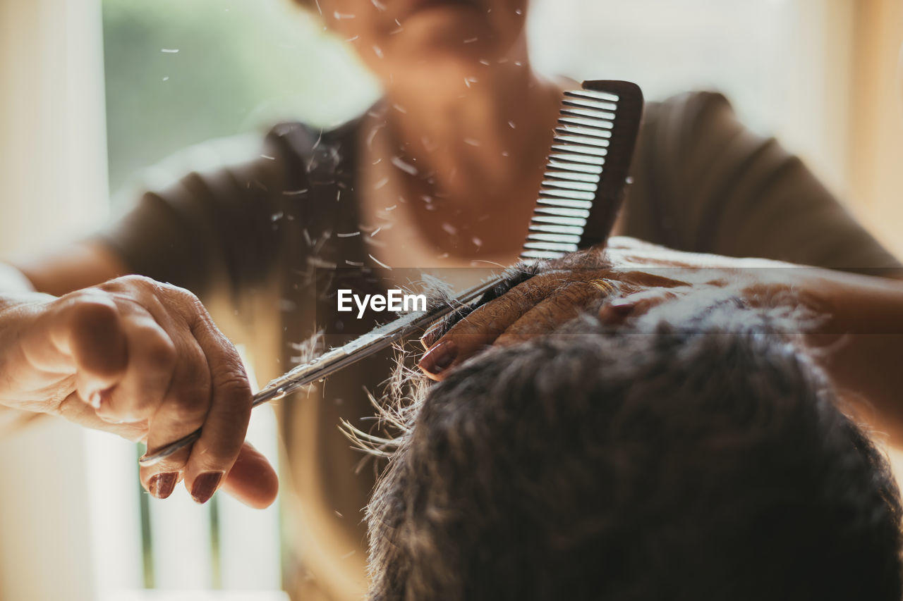 holding, comb, indoors, women, lifestyles, real people, hairdresser, adult, body care, people, human hair, hairstyle, hair, occupation, selective focus, cutting hair, scissors, focus on foreground, two people, combing, hand, skill, hair care