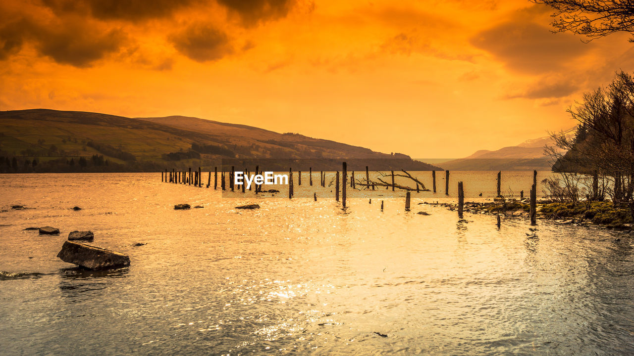 water, sky, scenics - nature, beauty in nature, cloud - sky, tranquil scene, tranquility, mountain, sunset, waterfront, nature, no people, orange color, sea, idyllic, non-urban scene, wooden post, outdoors, post