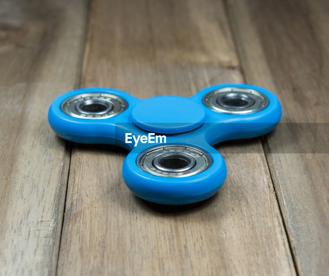 High Angle View Of Blue Fidget Spinners On Wooden Table