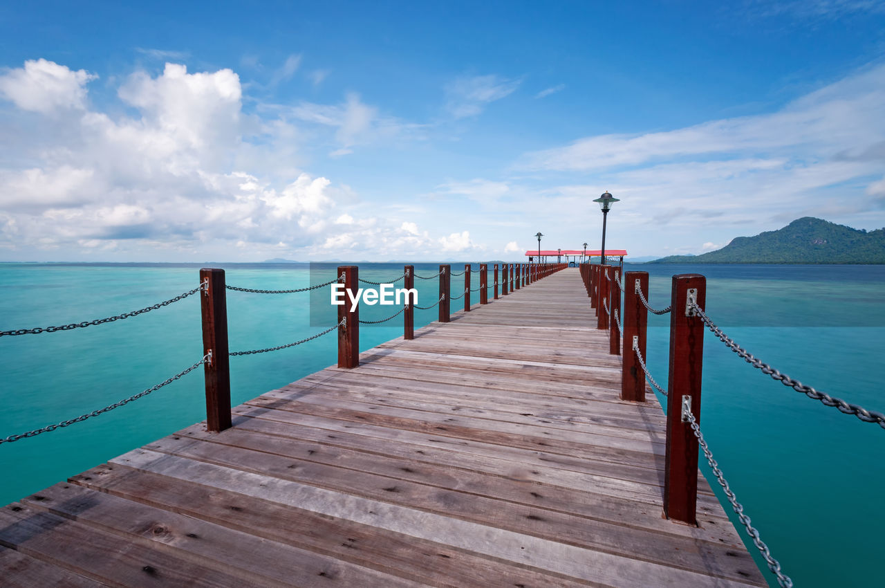 sky, water, sea, cloud - sky, pier, beauty in nature, wood - material, scenics - nature, tranquility, tranquil scene, railing, nature, built structure, no people, day, blue, the way forward, direction, jetty, outdoors, horizon over water, wood paneling, wood, long, wooden post, turquoise colored