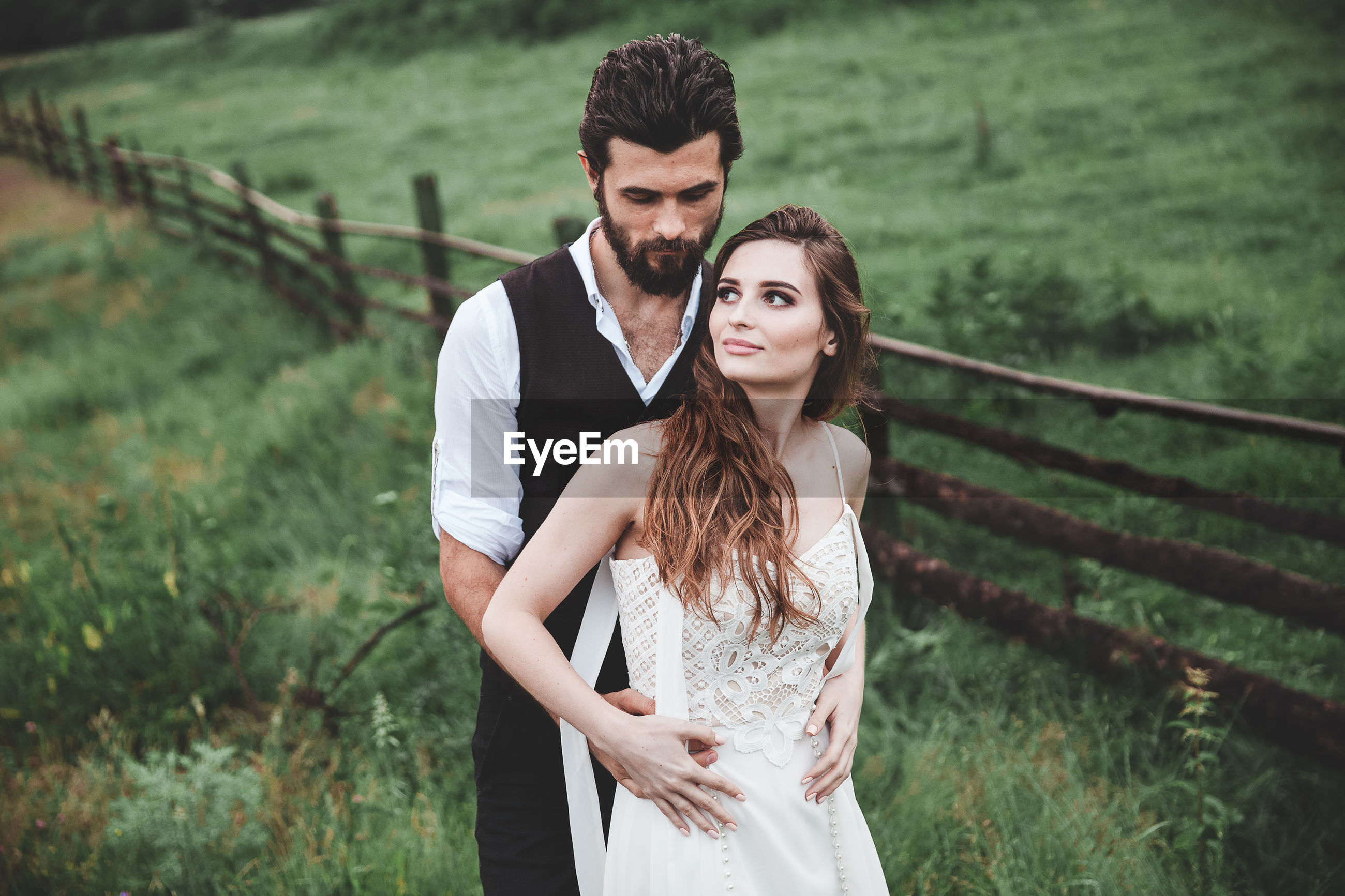 Wedding couple looking away while standing on field