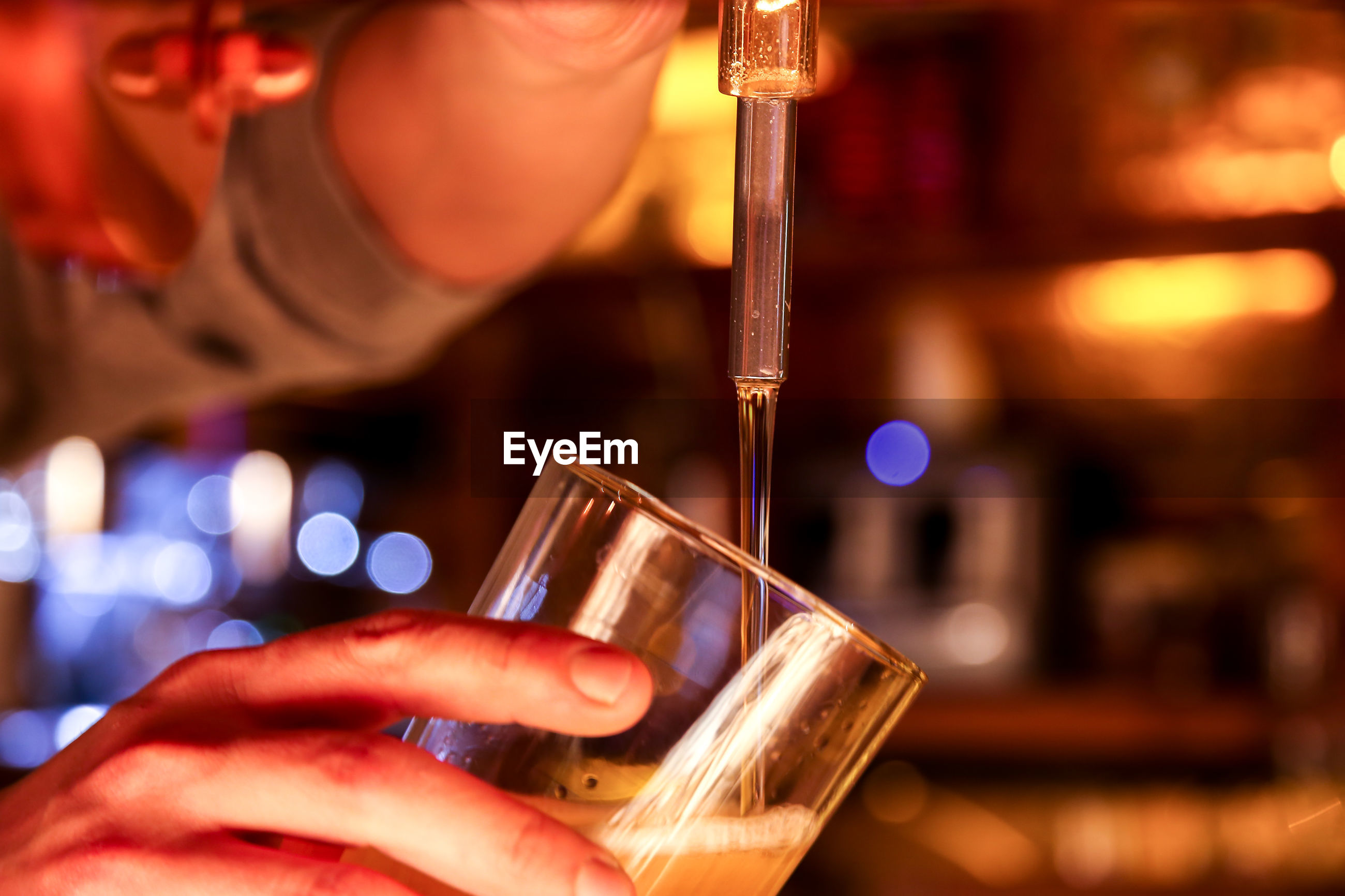 Close-up of man filling beer in glass from faucet at bar