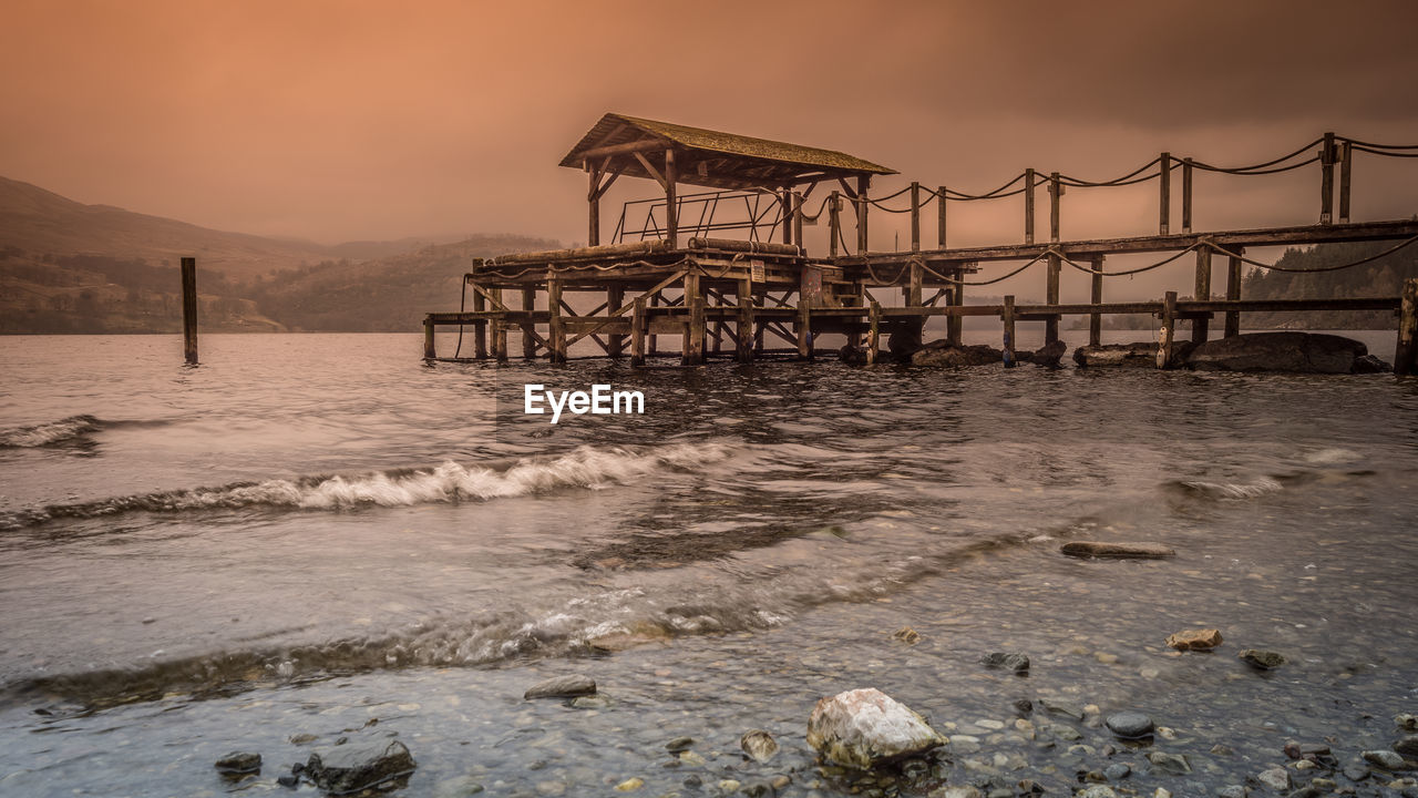 water, sky, architecture, built structure, sea, sunset, nature, pier, land, beach, beauty in nature, no people, scenics - nature, motion, wave, mountain, bridge, connection, outdoors