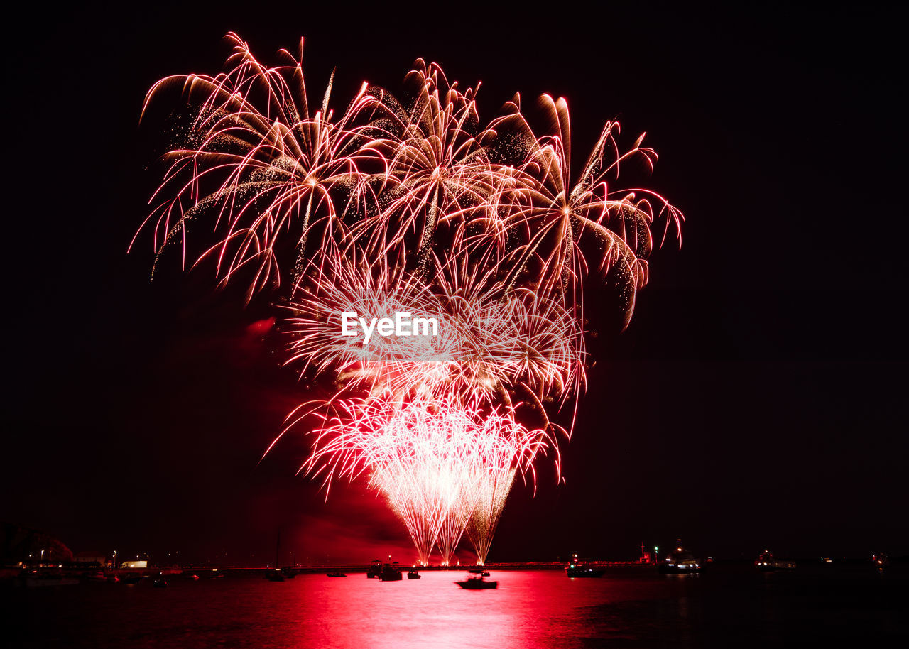 night, illuminated, firework, motion, firework display, arts culture and entertainment, exploding, celebration, sky, glowing, event, long exposure, nature, firework - man made object, multi colored, water, low angle view, no people, light, sparks, outdoors, explosive