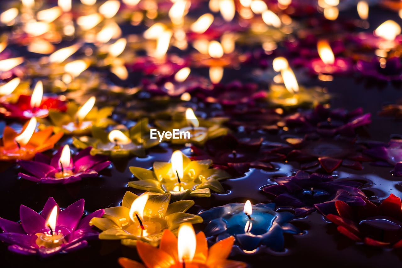 burning, illuminated, glowing, candle, fire, fire - natural phenomenon, flame, spirituality, belief, religion, heat - temperature, close-up, no people, large group of objects, lighting equipment, place of worship, nature, oil lamp, celebration, tea light, floating on water