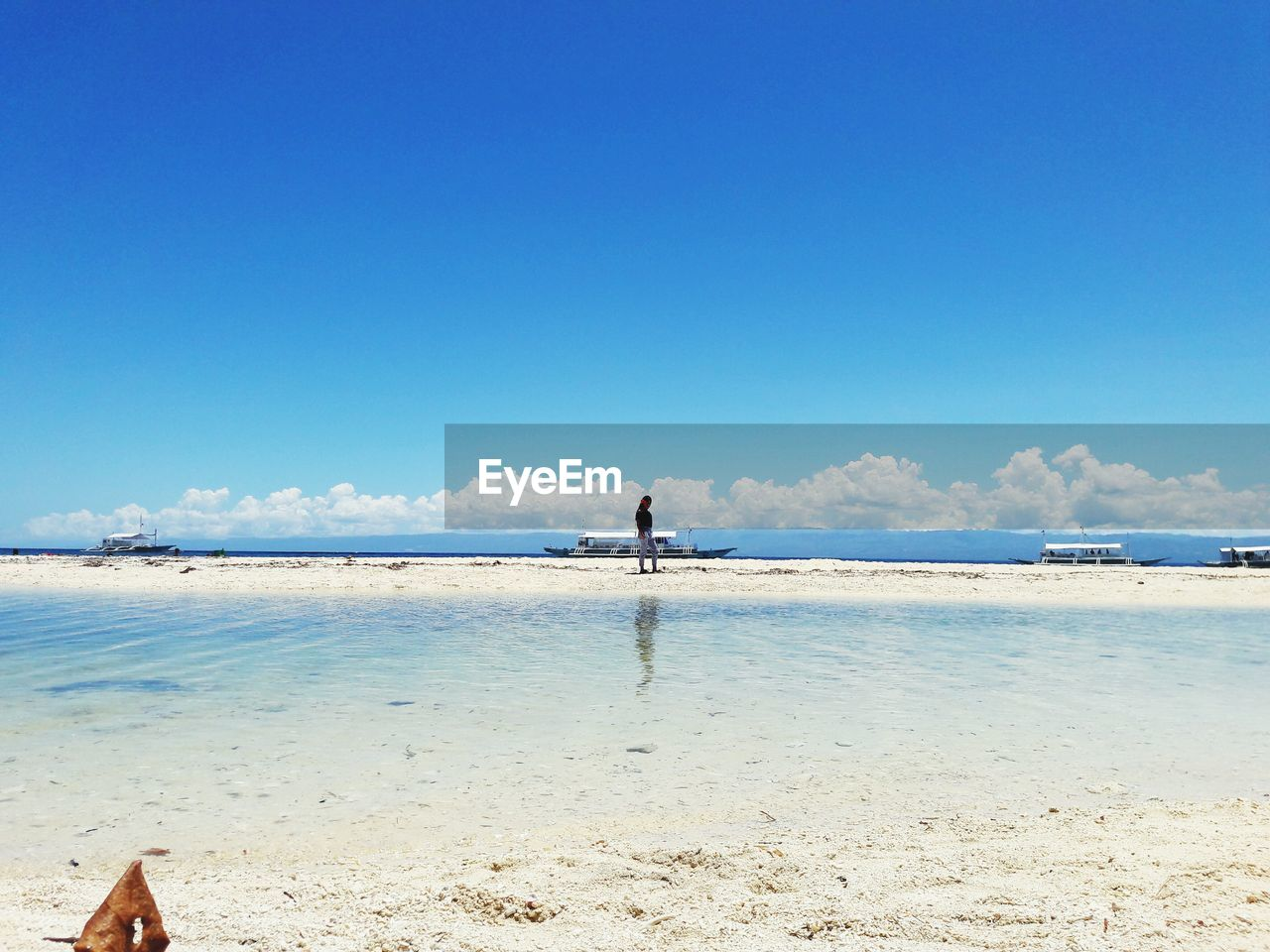 sky, sea, land, water, beach, beauty in nature, one person, scenics - nature, tranquility, nature, lifestyles, tranquil scene, blue, real people, leisure activity, day, copy space, horizon, idyllic, horizon over water, outdoors