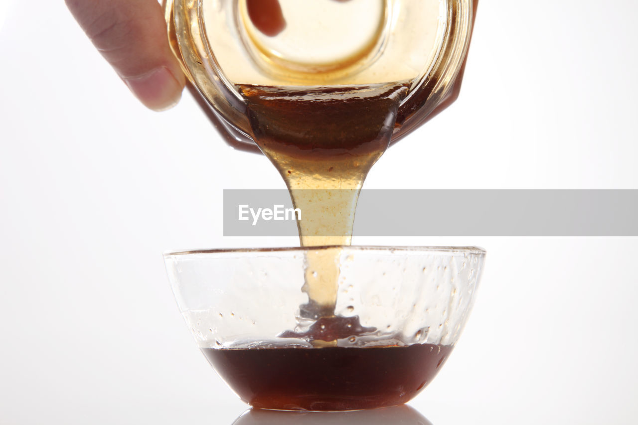 Cropped hand of person pouring honey from jar against white background