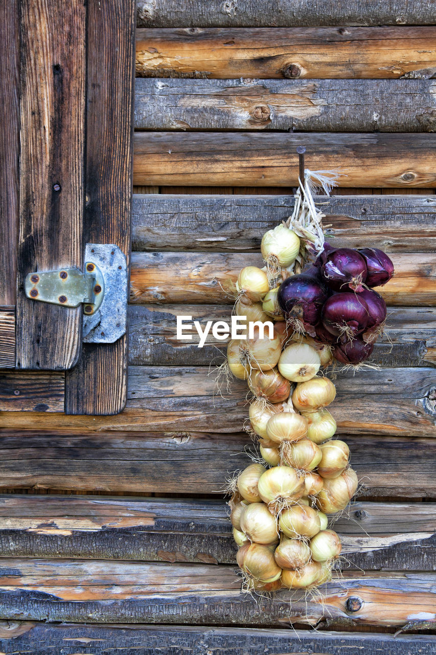 Onions Hanging From Wooden House Wall